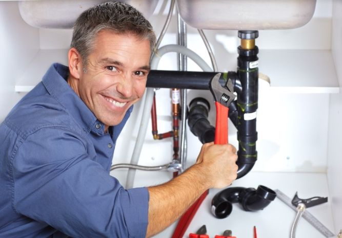 Smiling Plumber Repairing Sink Pipes